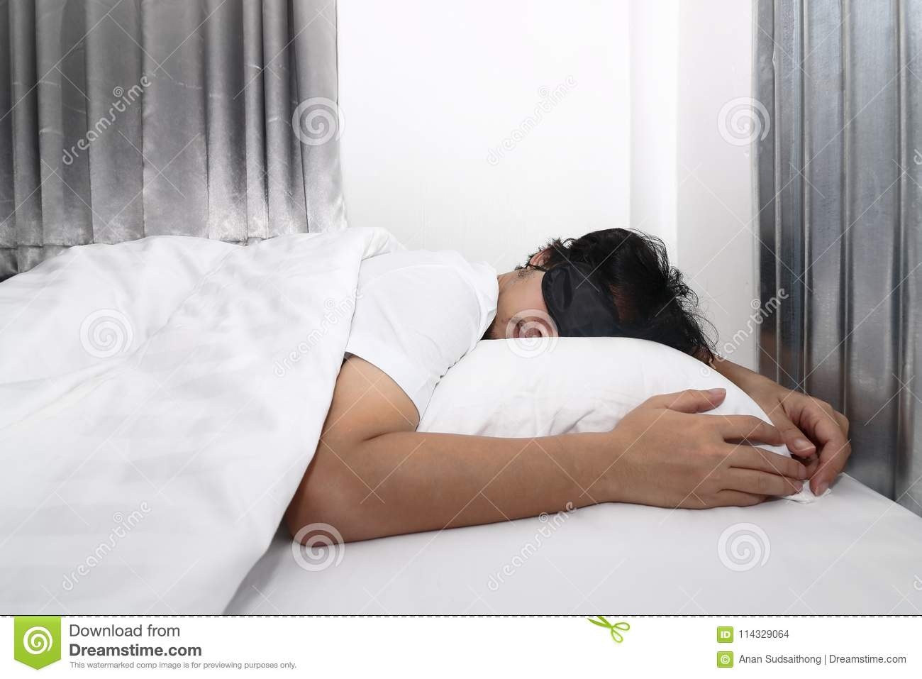 Young Asian Man With Blindfold Eye Mask Sleeping On The White Bed In Bedroom