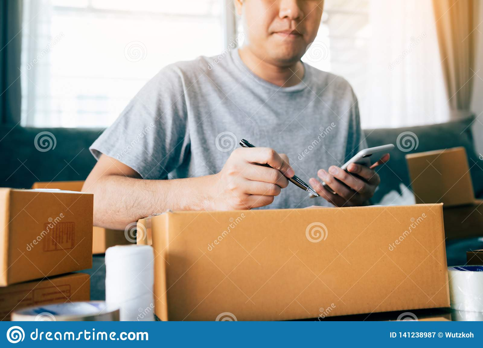 Young asian man business owner hands writing address on cardboard box at workplace or home office