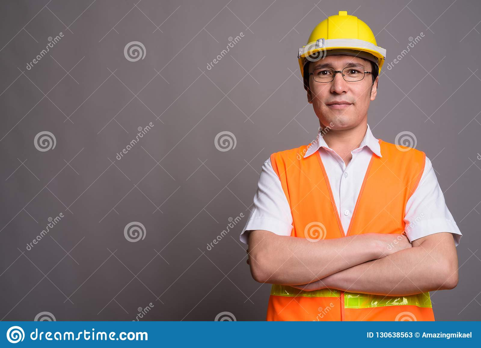 Young Asian man construction worker wearing eyeglasses against g