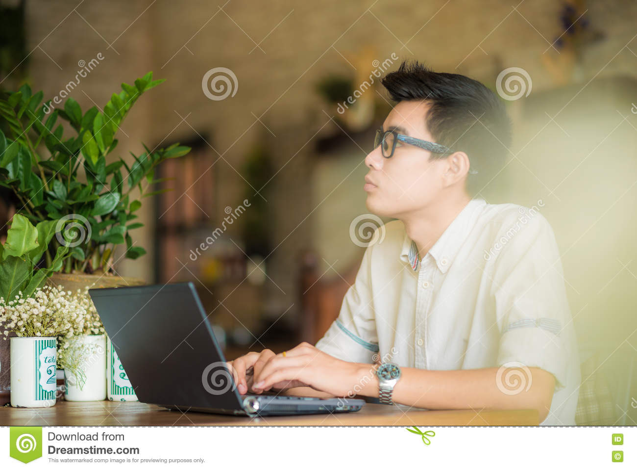 Young asian man drinking coffee in cafe and using laptop compute