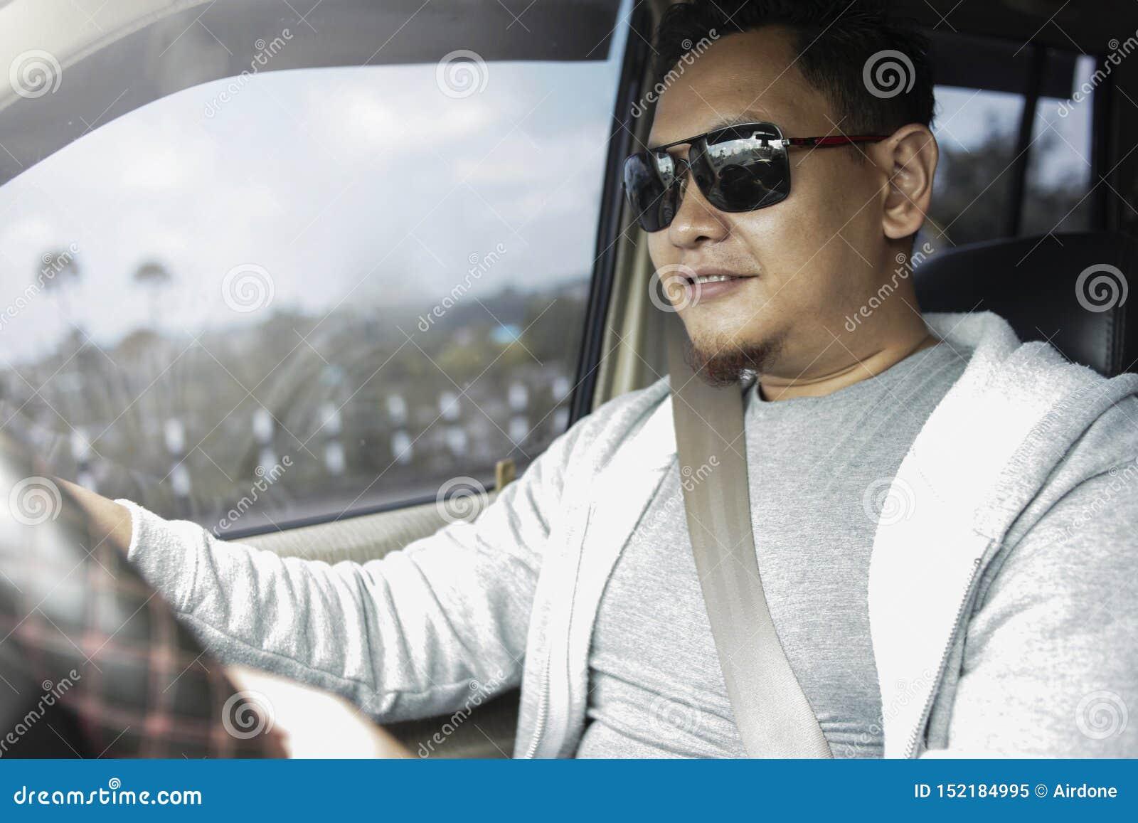 Young Asian Man Driving a Car
