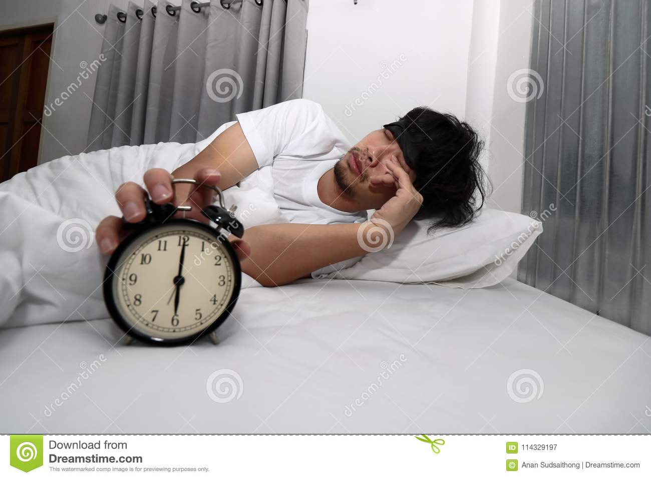 Young Asian man with eye mask wake up and stop alarm clock on the bed