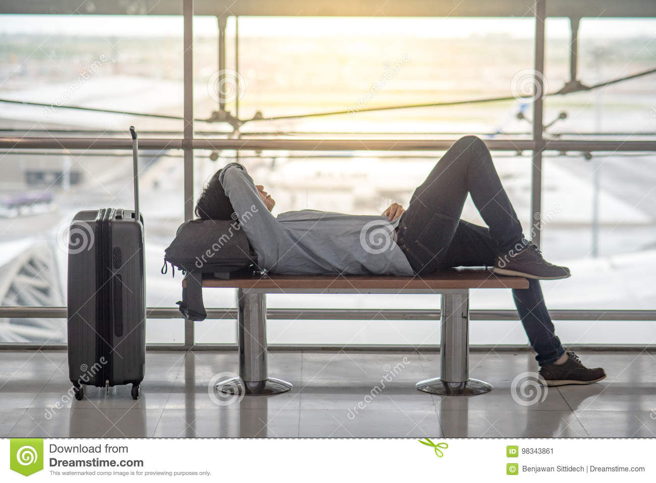 Young Asian man lying on bench in airport terminal