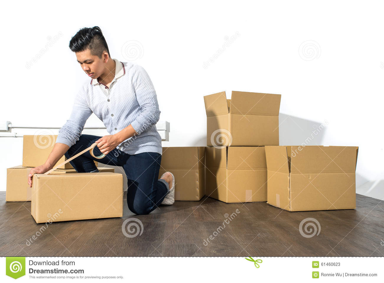 Young Asian Man Moving House Packing Cardboard Using