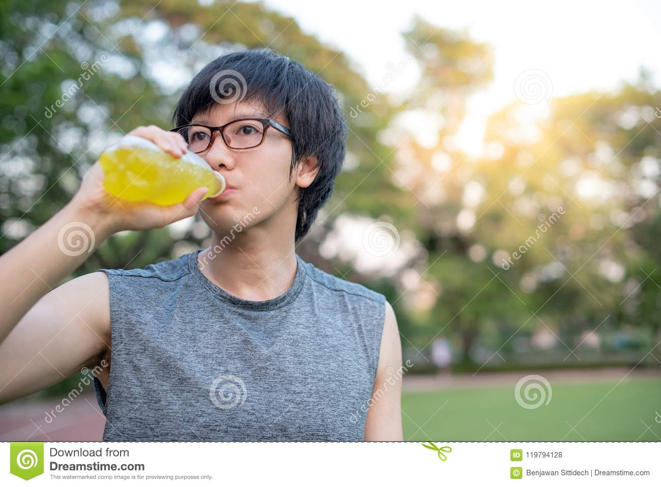 Young Asian Man Runner Drinking Energy Drink After Running In Th ...