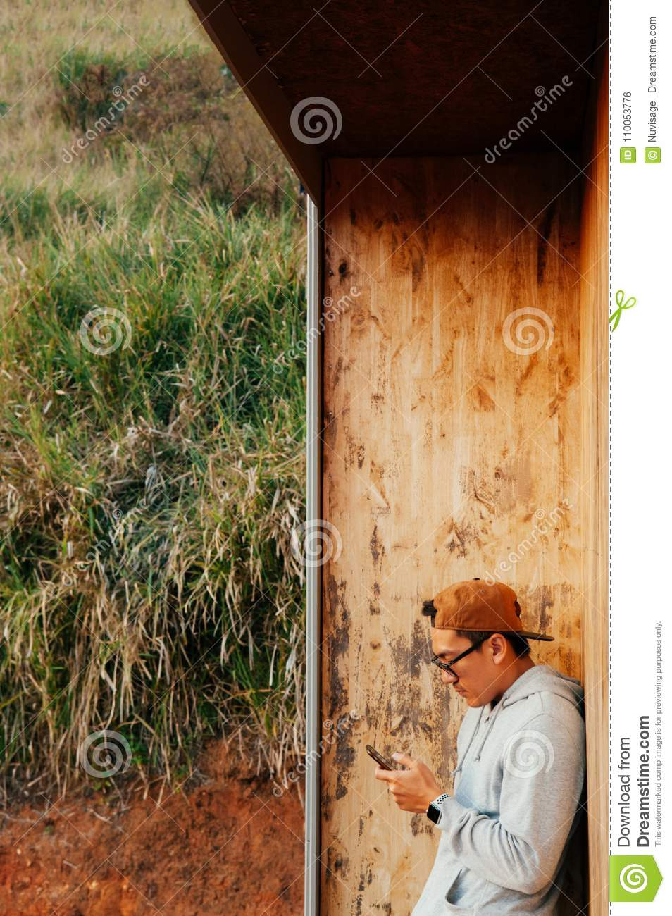 Young asian man using mobile phone stand against wooden wall wit