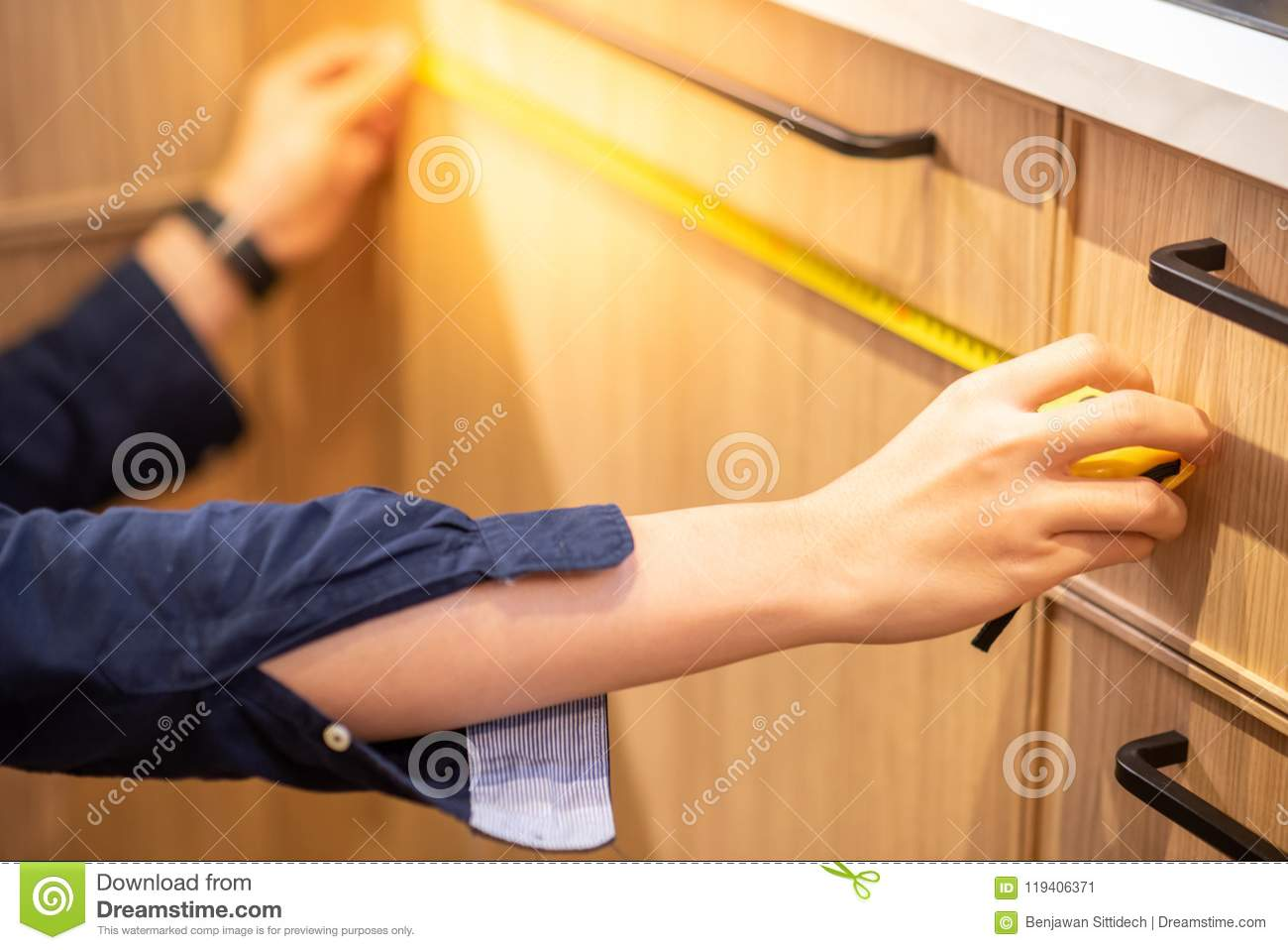 Young Asian Man Using Tape Measure For Measuring Furniture