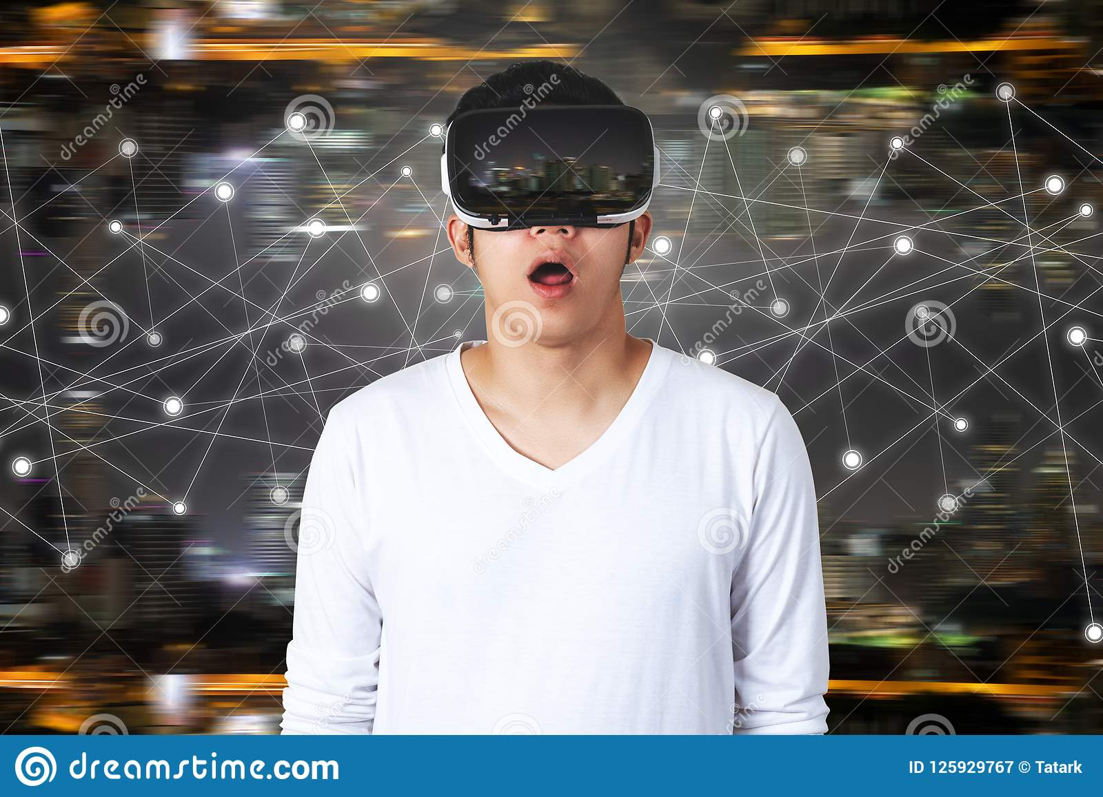 850ec888644 A young Asian man in casual white outfit wearing VR glasses watching video  with open mouth feeling excited