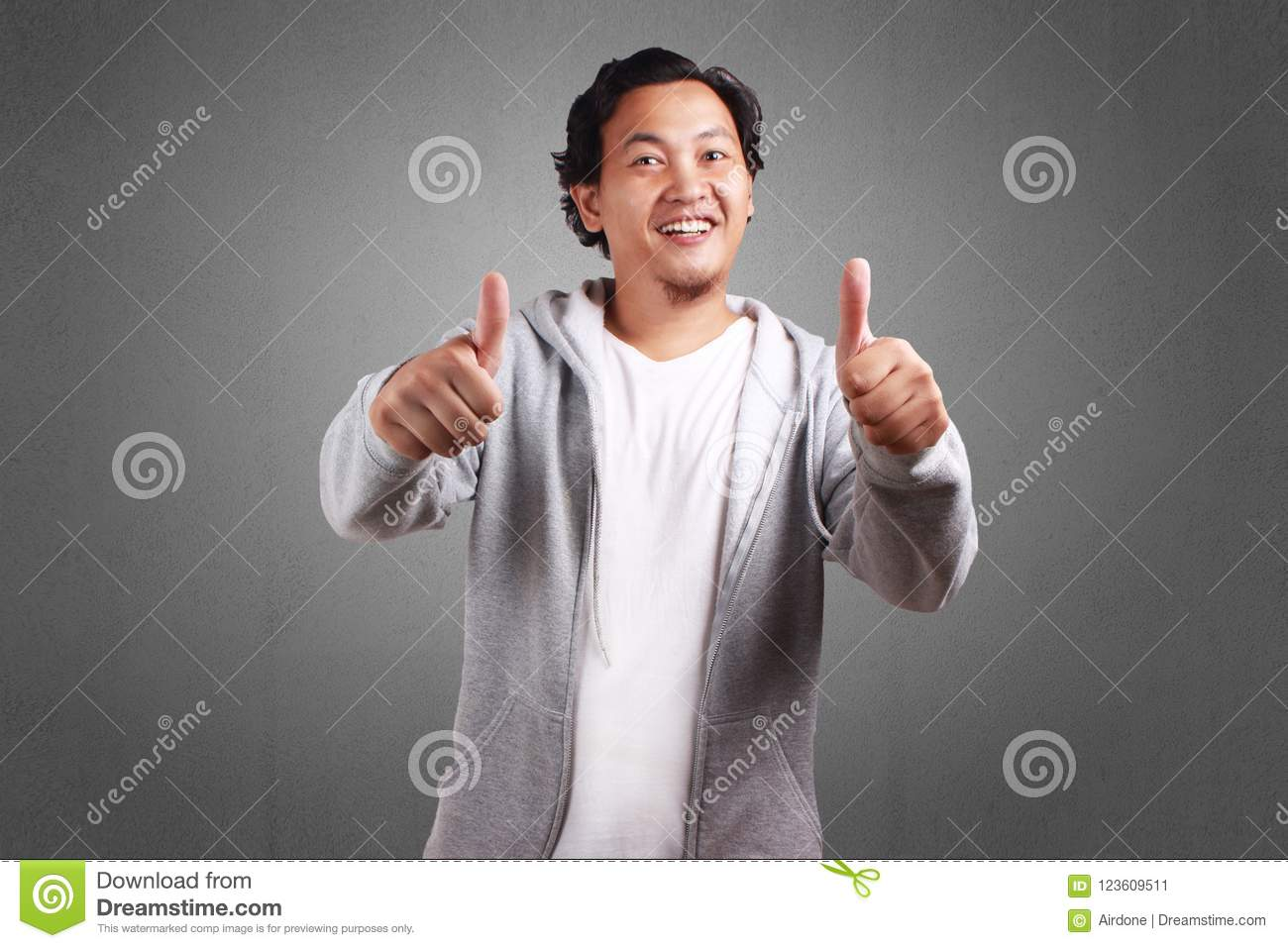 Young asian man wearing a jacket, Smiling with two thumbs up, Looking at  camera