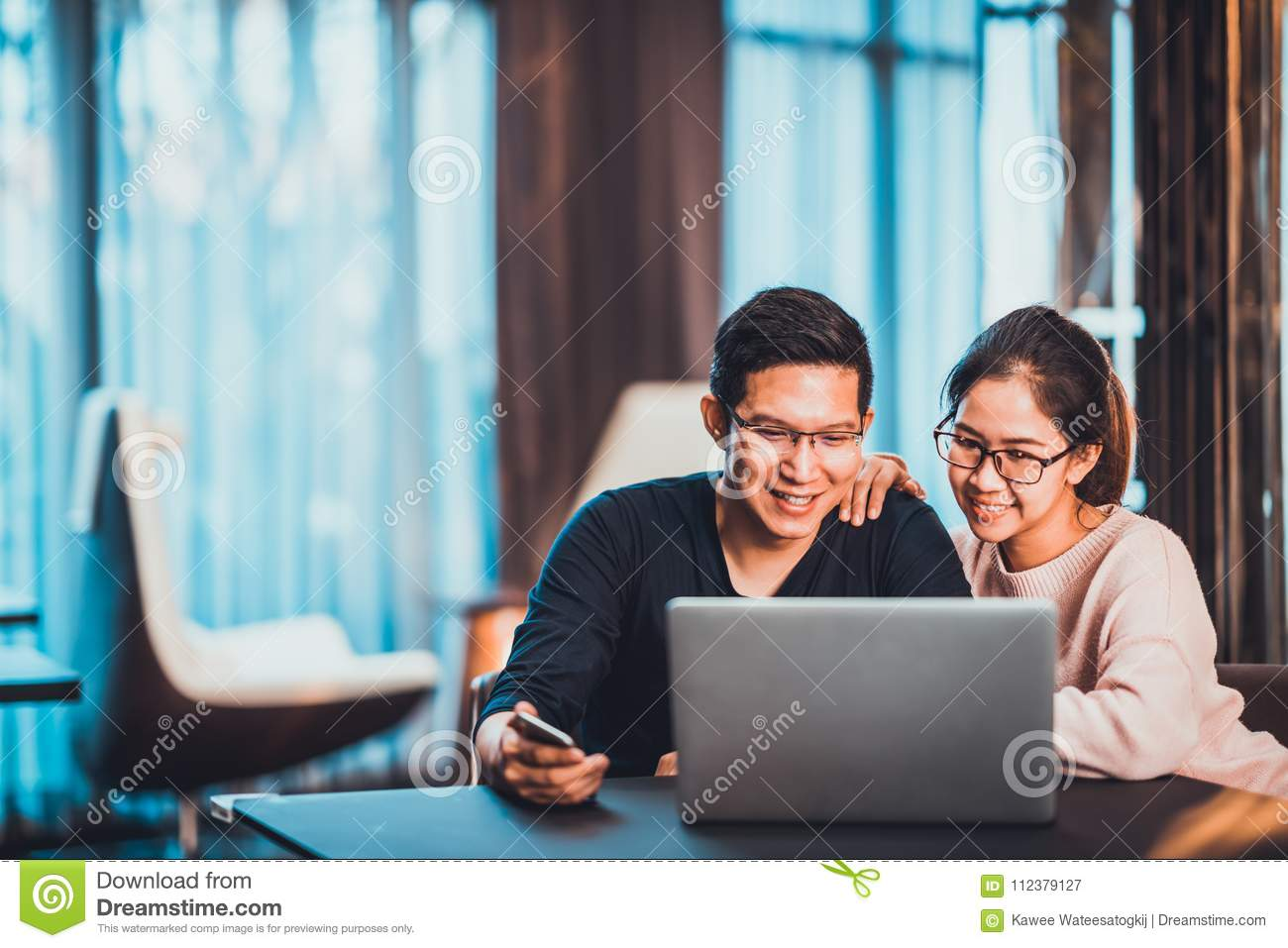 Young Asian married couple working together using laptop at home or modern office with copy space. Startup family business concept