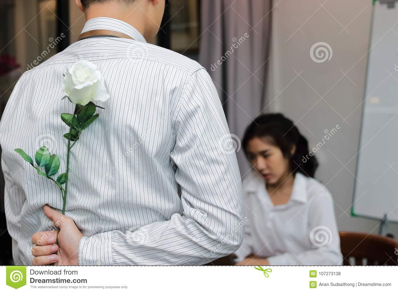 Young Asian man hiding a white rose behind his back for surprise girlfriend in valentines day. Love and romance in office concept.