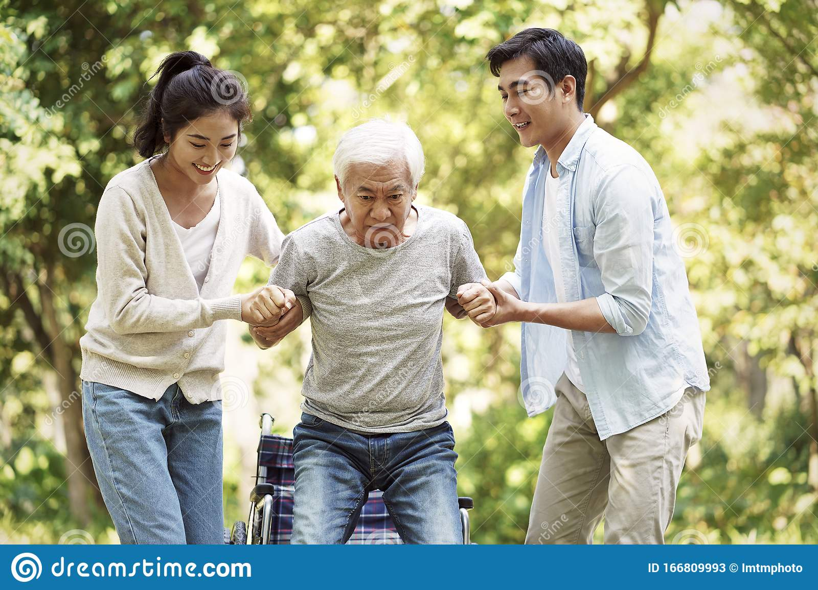 Young Asian Couple Helping Old Man Stand Up Stock Image