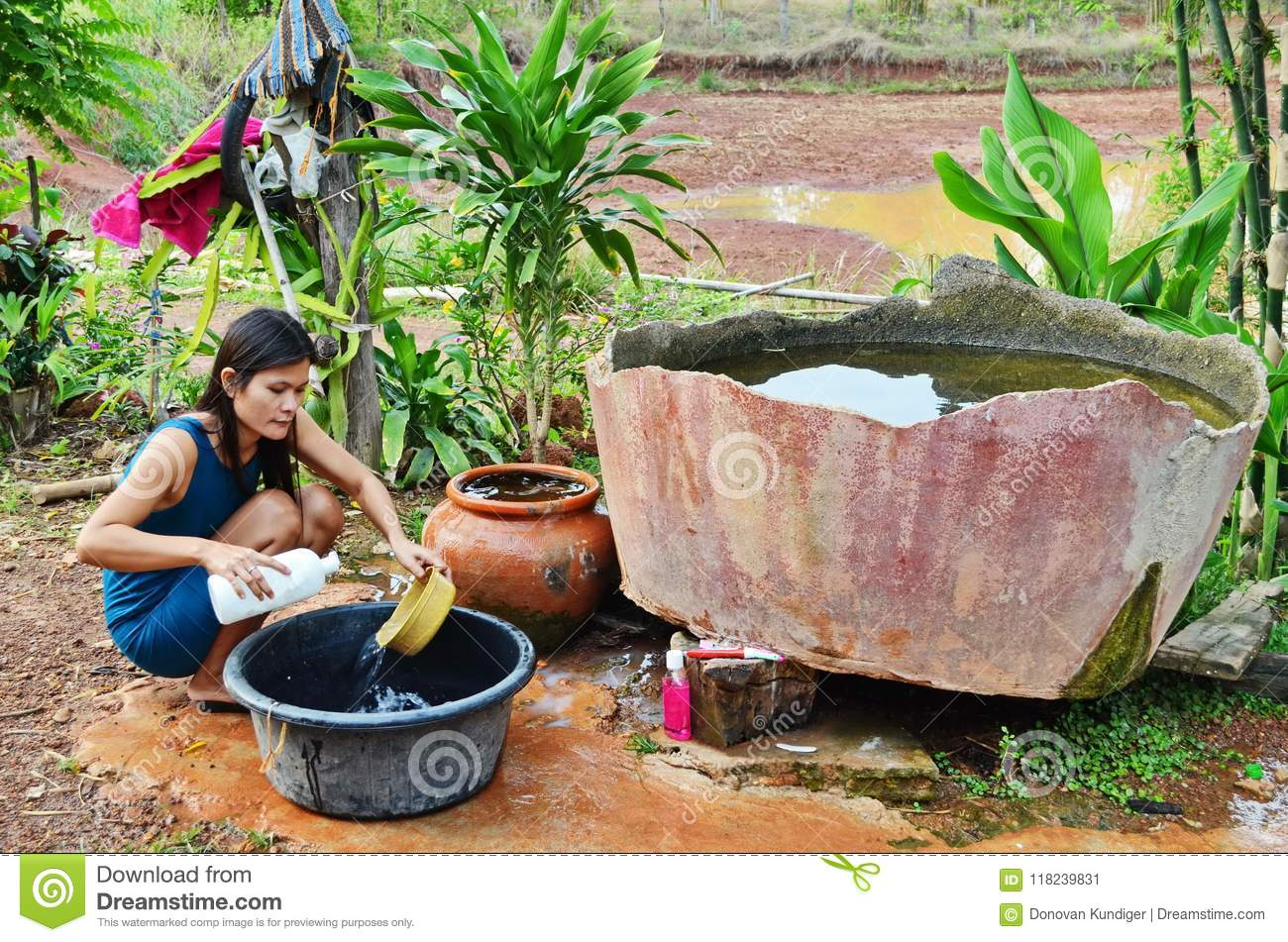 Young Asian mother washes dishes in primitive kitchen.