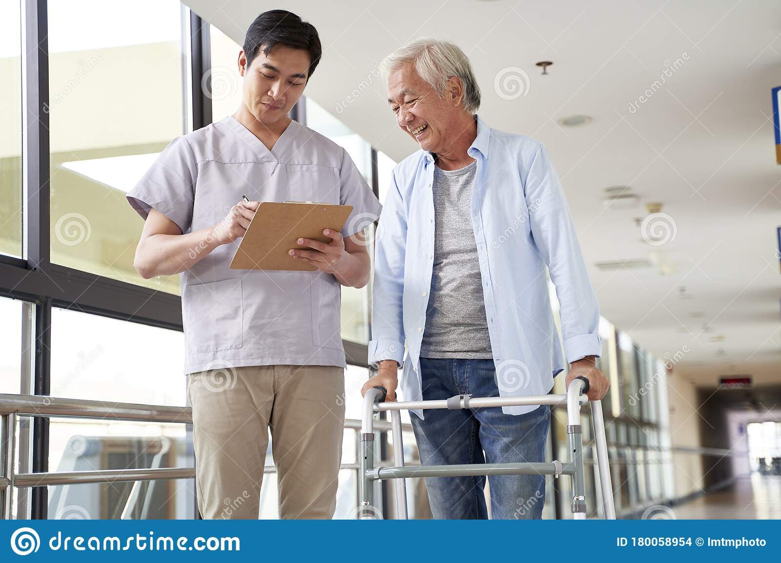 Young Asian Physical Therapist Working With Old Man Stock