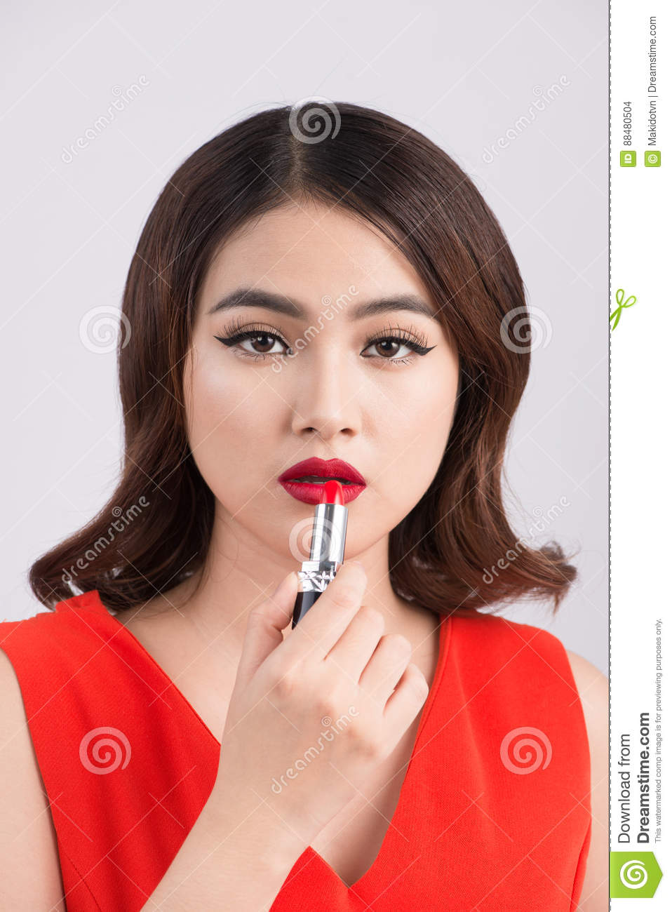 Young asian woman with dark hair using red lipstick.