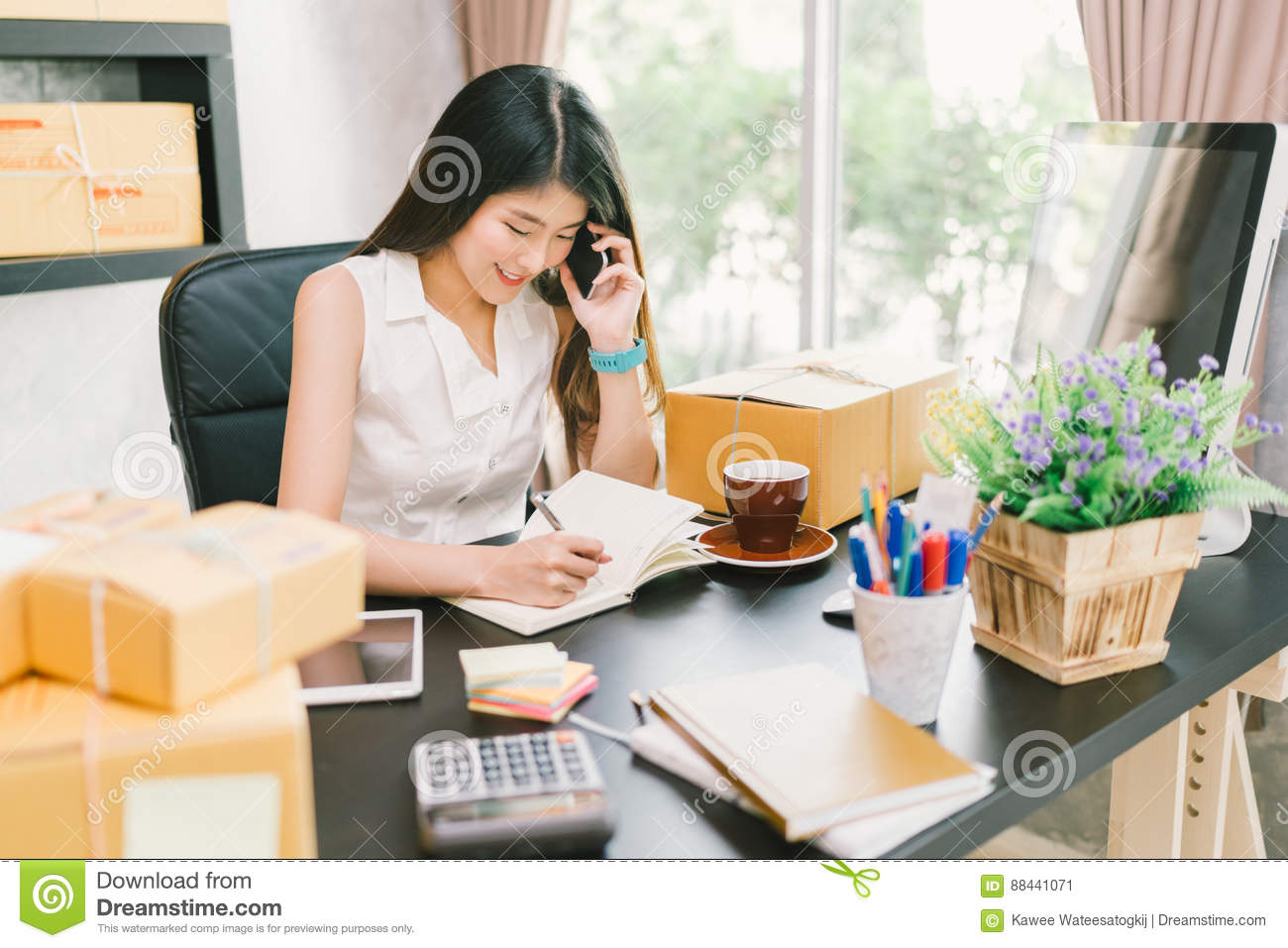 Young Asian small business owner working at home office, using mobile phone and taking note on purchase orders