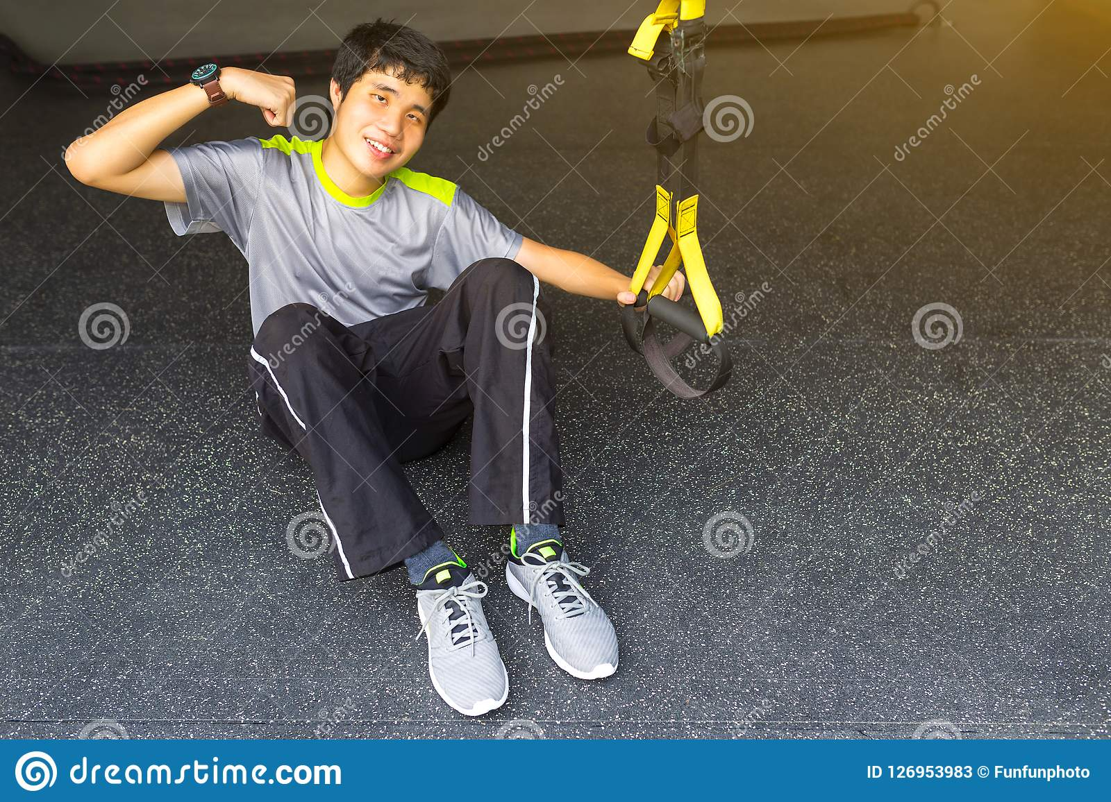 Young asian strong man holding lifeline pull up revolution getting ready for exercise in fitness.