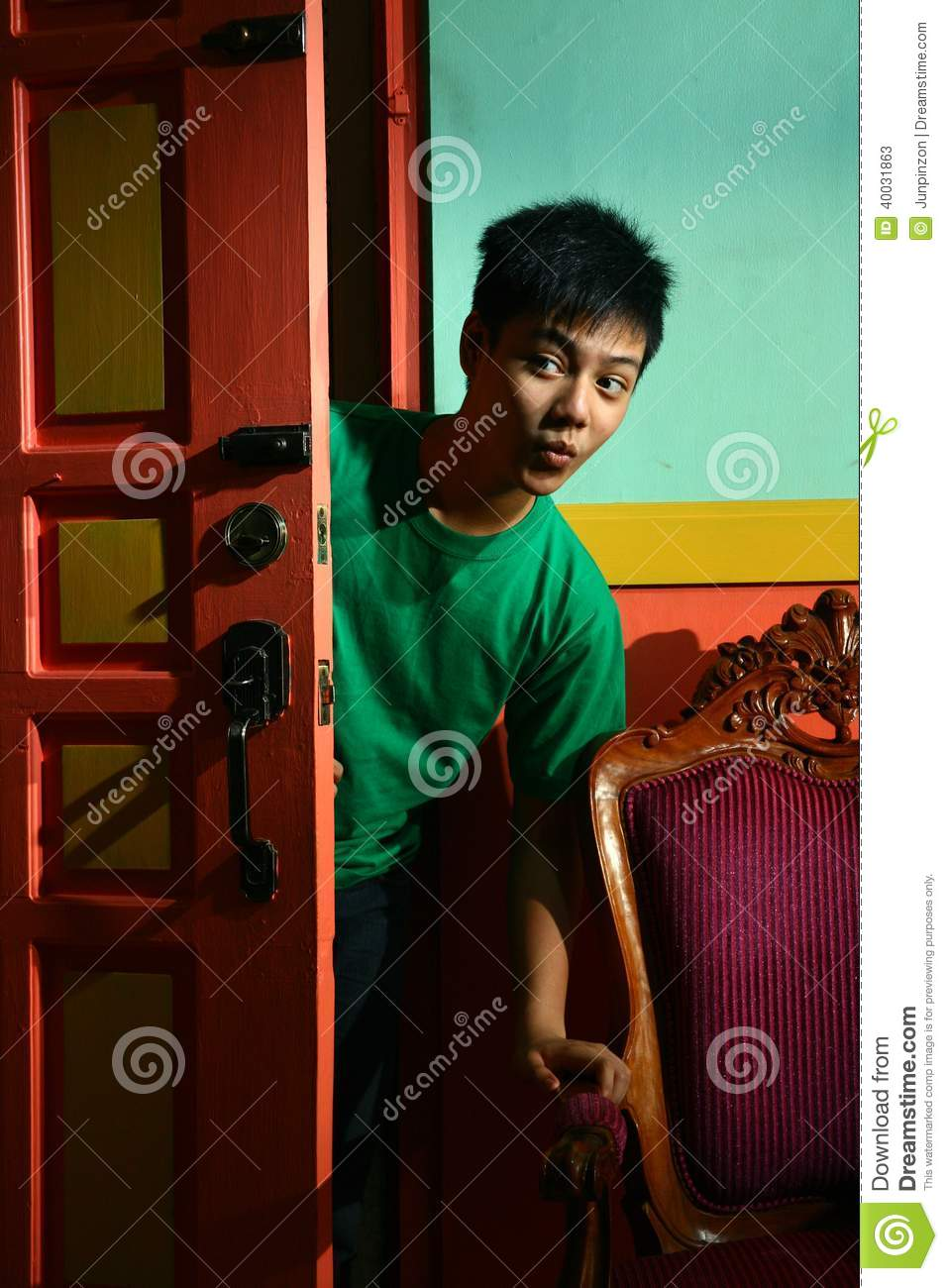 Young asian teen peeking and sneaking in into a living room