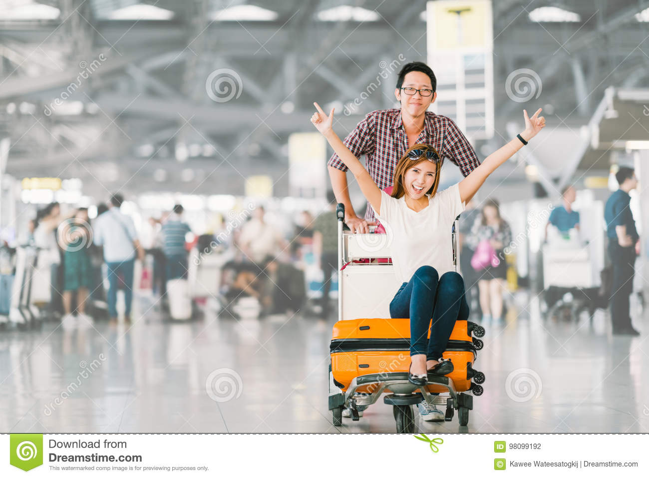 Asian tourist couple happy and excited together for the trip, girlfriend sitting and cheering on baggage trolley or luggage cart