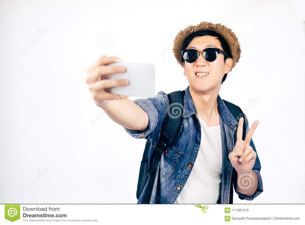 Young Asian tourist with hat smiling and holding smartphone taking a selfie photo isolated over white background.