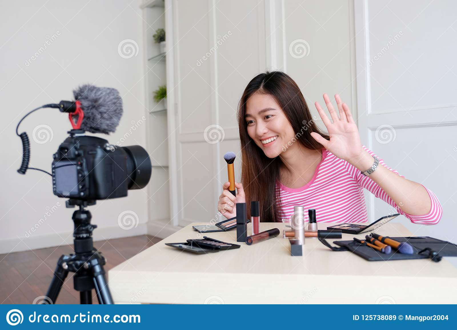 Young asian woman beauty blogger showing how to make up video tu