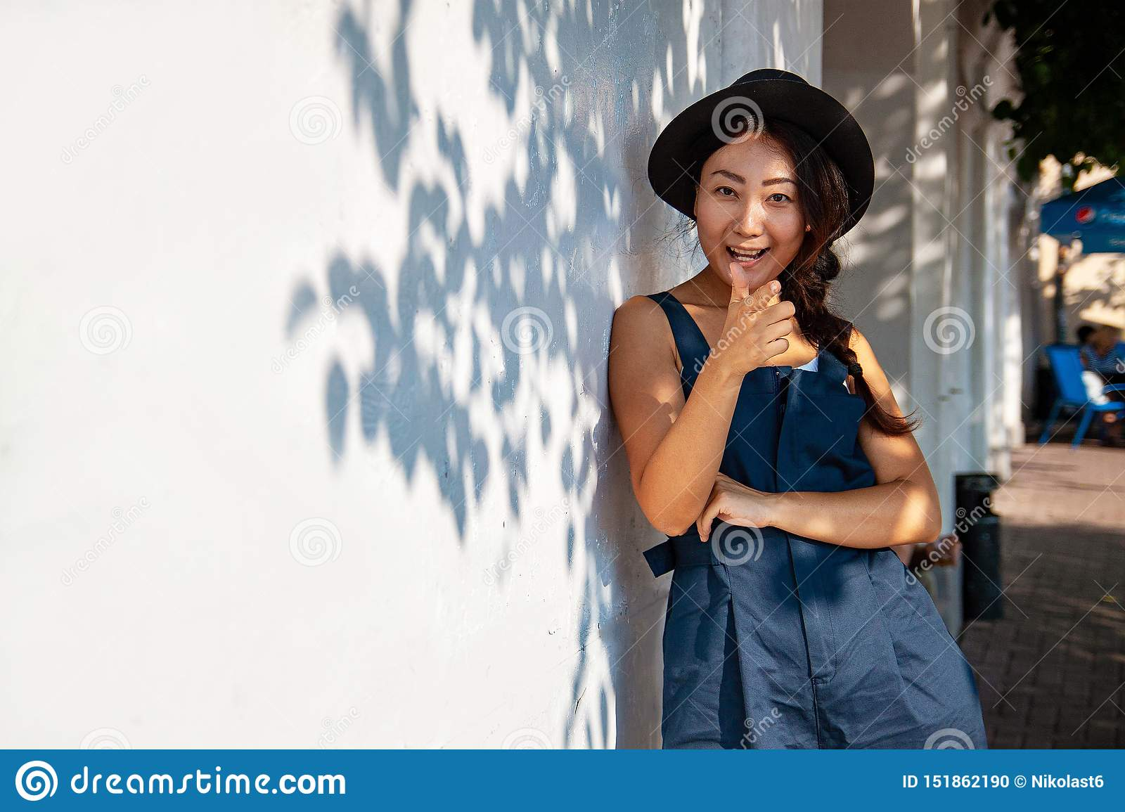 Beautiful leaves of maple tree glowing in sunlight.Young asian woman in casual against white wall with shadows from tree. Copy spa