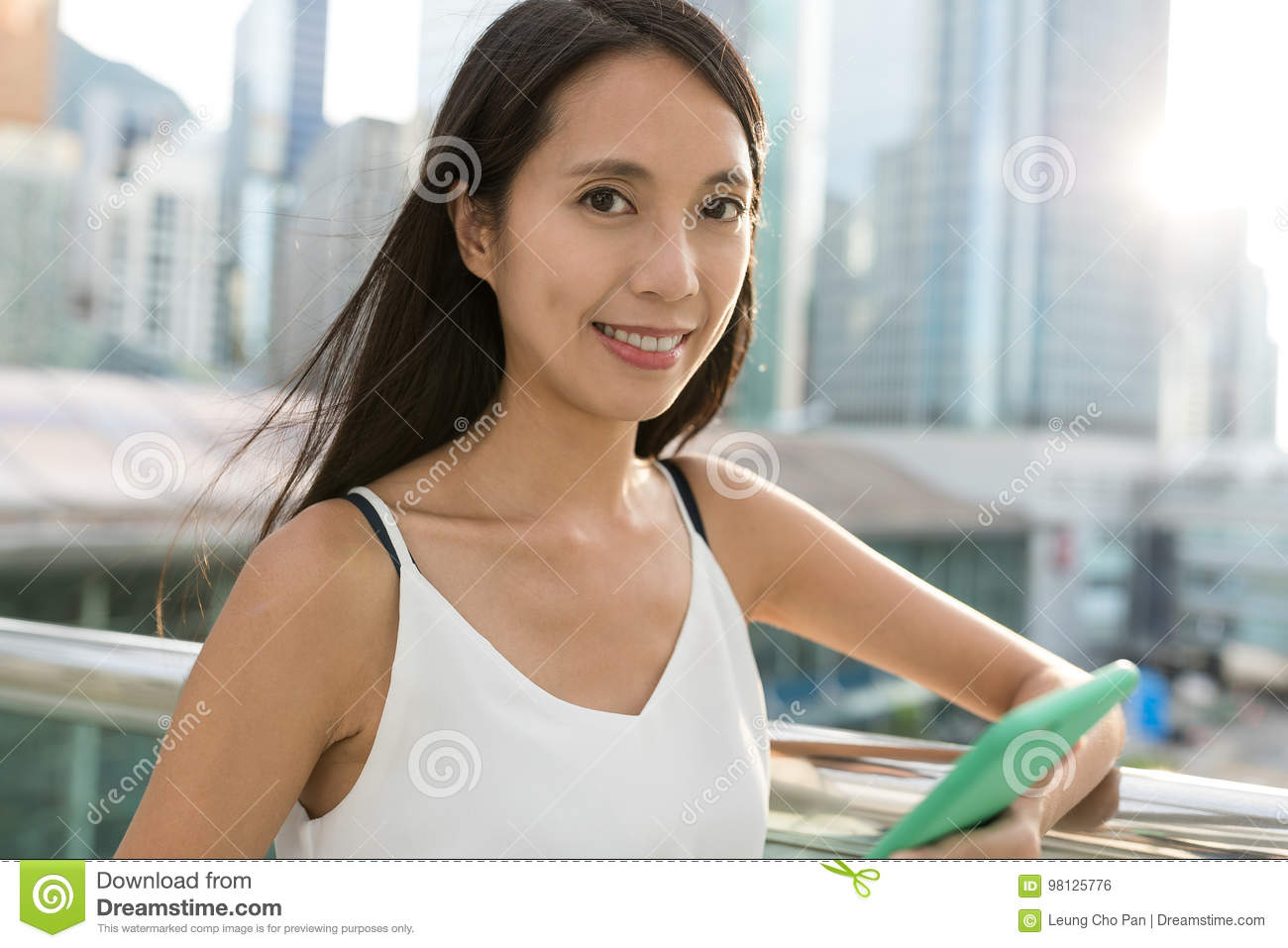 Young asian woman holding cellphone in the city