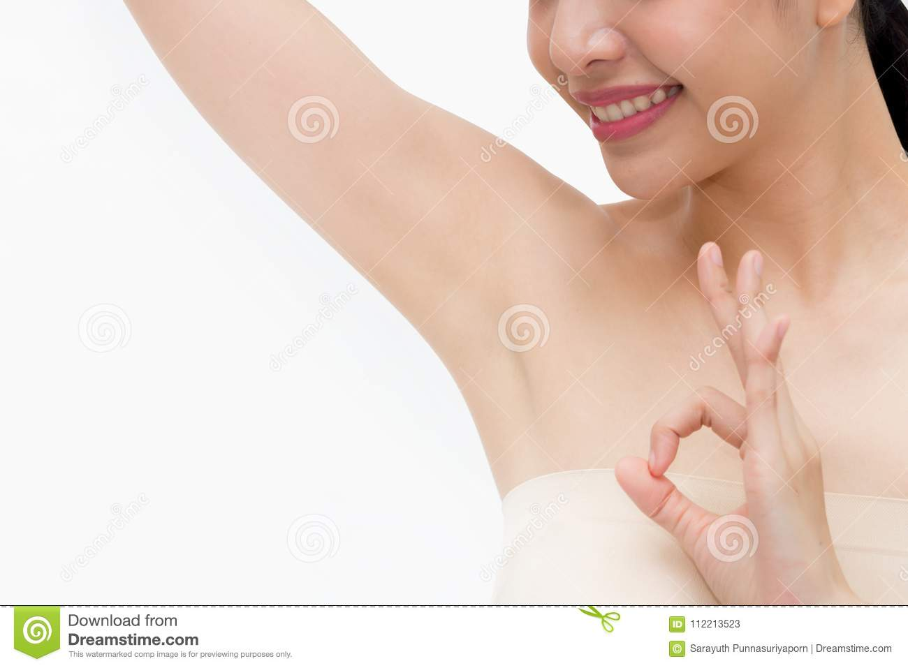 Young Asian woman lifting hands up to show off clean and hygienic armpits or underarms and giving okay sign