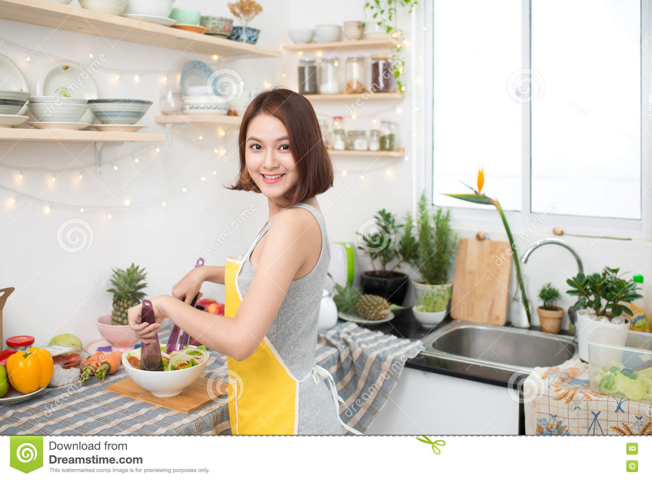 young asian woman making salad in kitchen smiling and laughing h