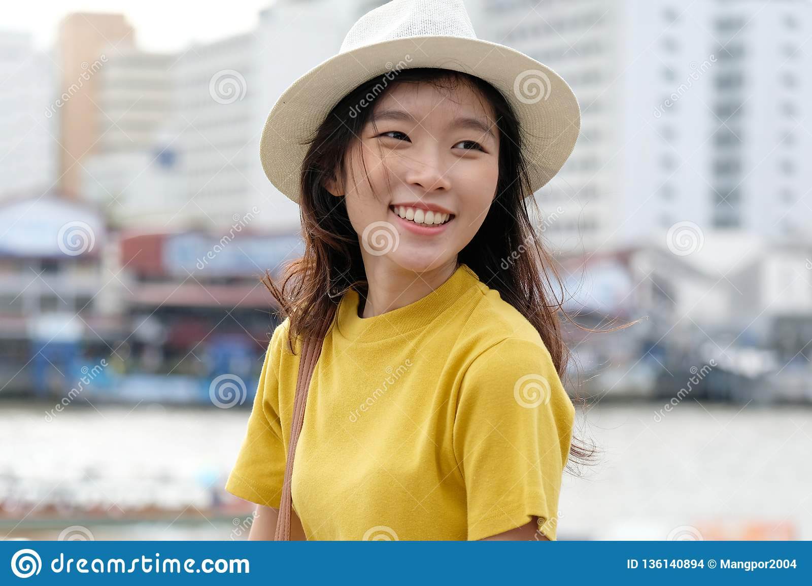 Young asian woman portrait smiling with happiness at city outdoors background, happy moment, casual lifesyle, travel blogger