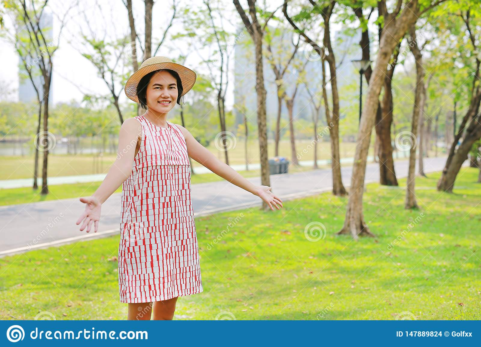 Young Asian woman raising arms and smile in nature park
