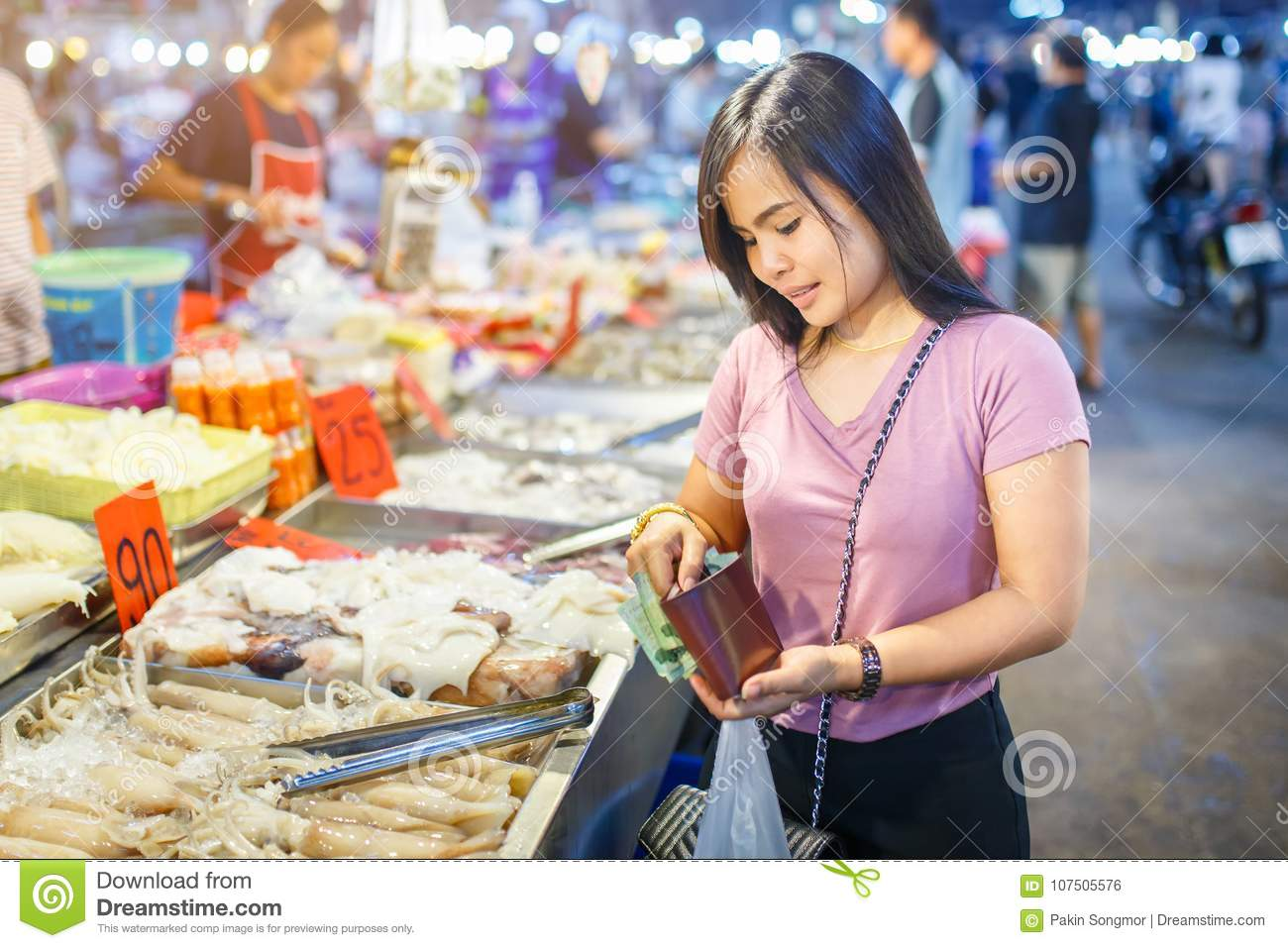 Young asian woman shopping for squid on ice in local market stall with fresh seafood
