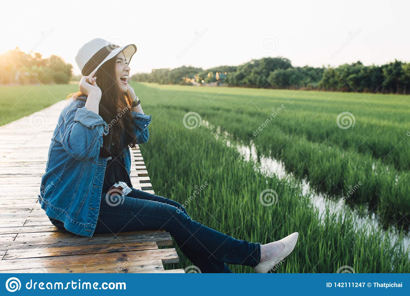 Young asian woman smiling in hat. Girl enjoying at beautiful nature with sunset. Travel Summer Holiday Vacation and Relaxation