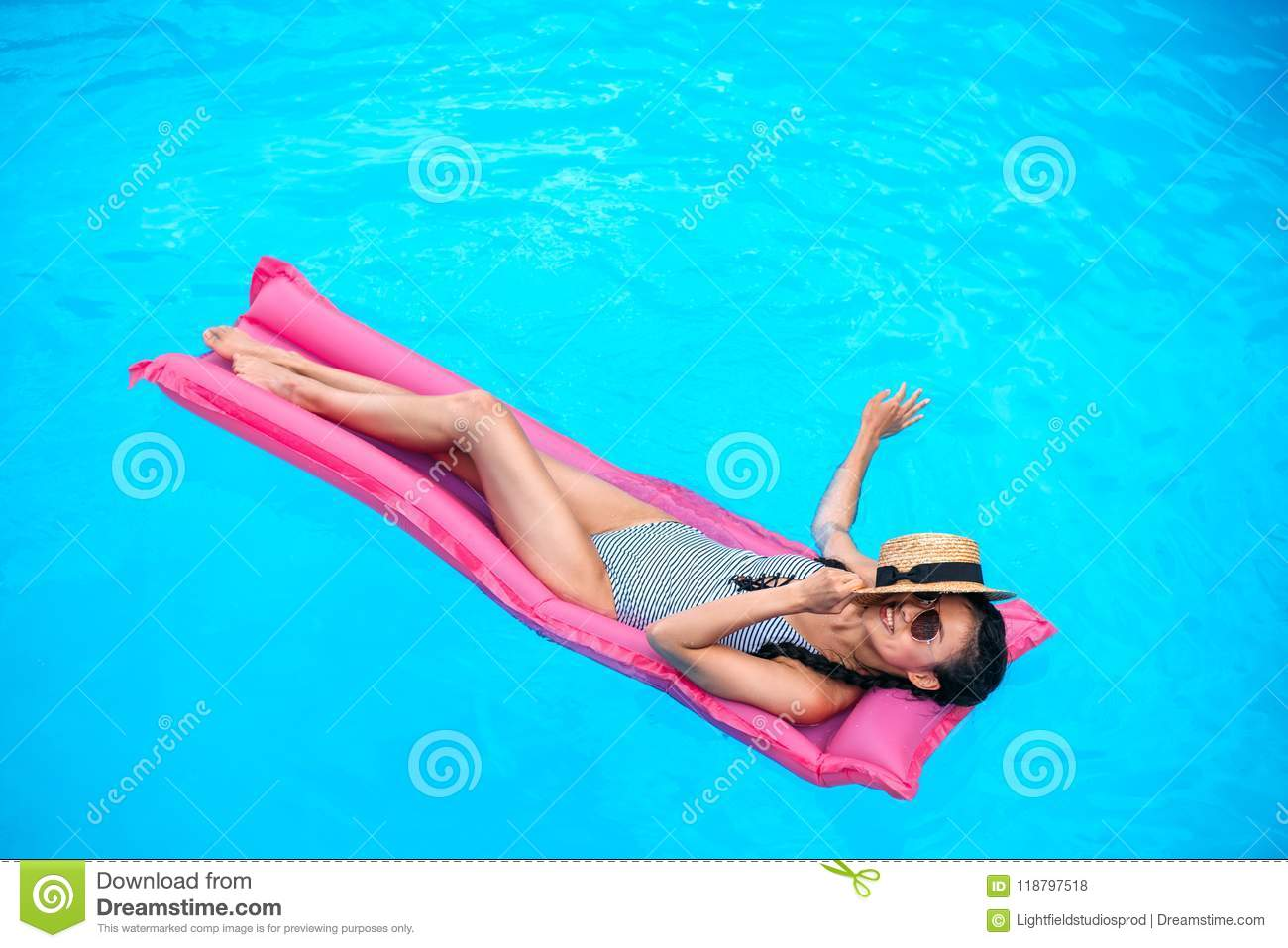 Young asian woman with straw hat covering face floating on inflatable mattress