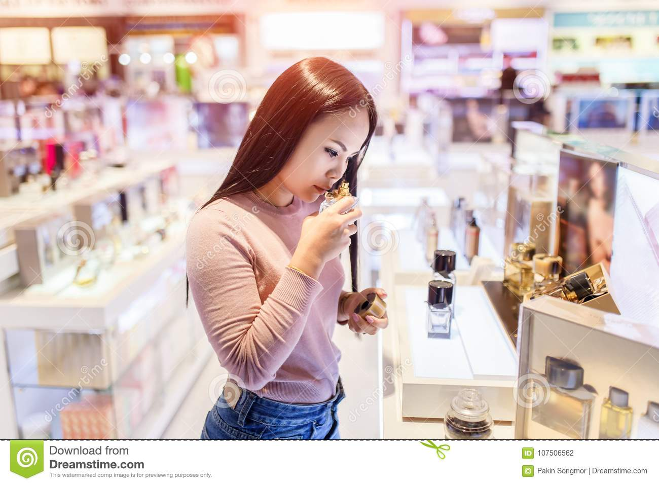 Young asian woman testing and choose to buy perfume in duty free store at international airport