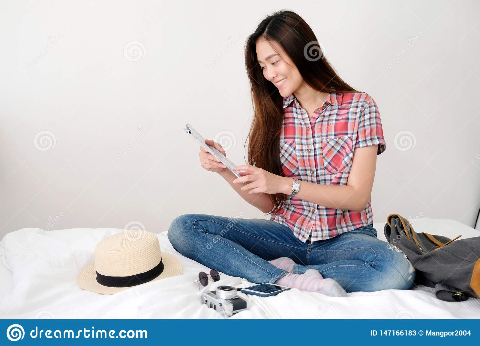 Young asian woman traveler holding map while sitting on bed with hat, camera, eyeglasses, bag and smartphone with happiness