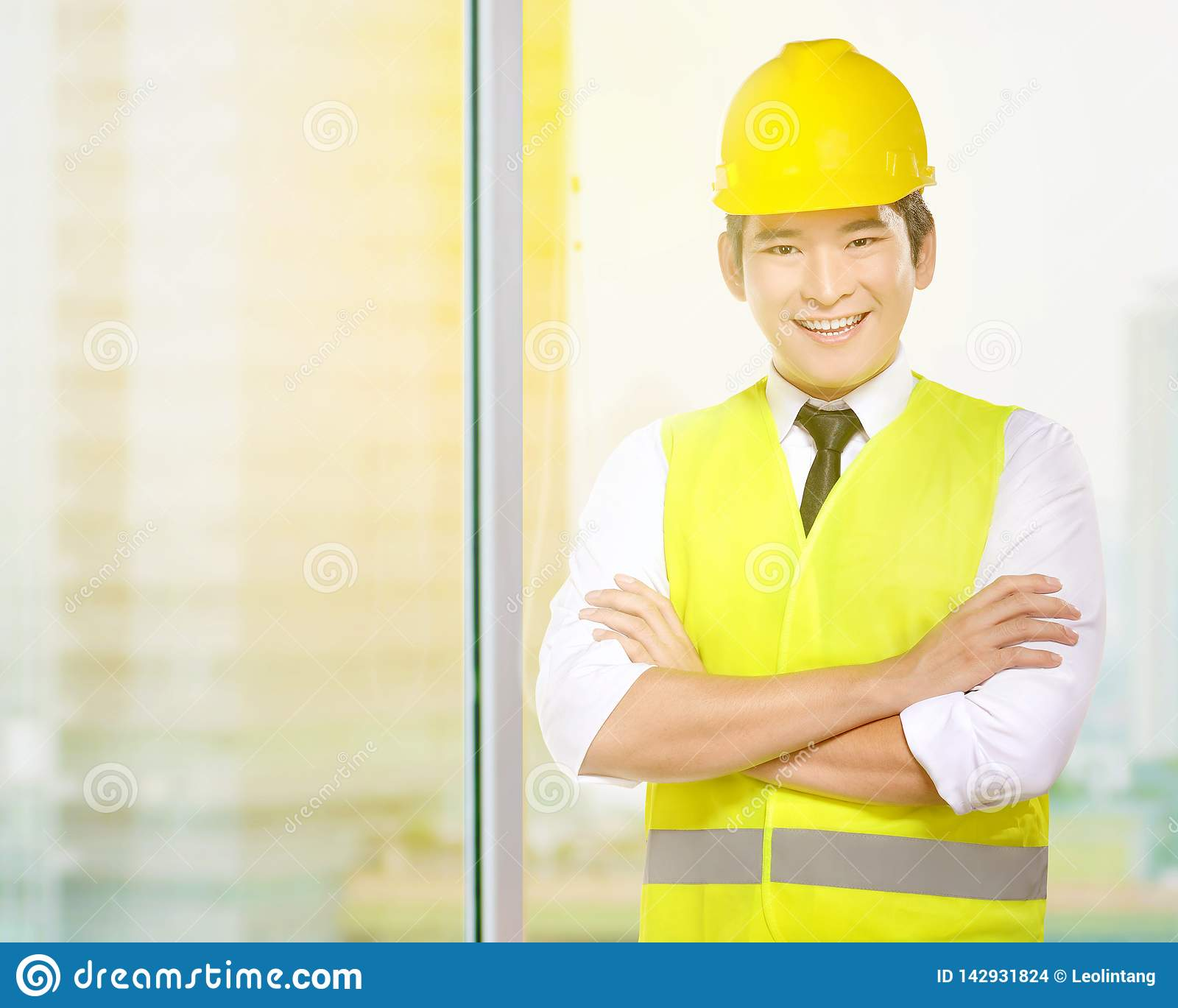 Young asian worker man in safety vest and yellow helmet standing in the office room