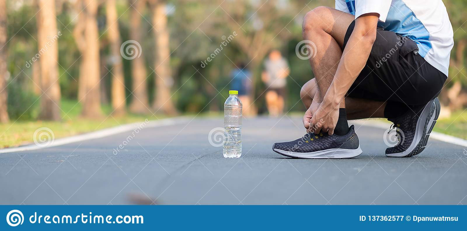 Young athlete man tying running shoes in the park outdoor. male runner ready for jogging on the road outside. asian Fitness