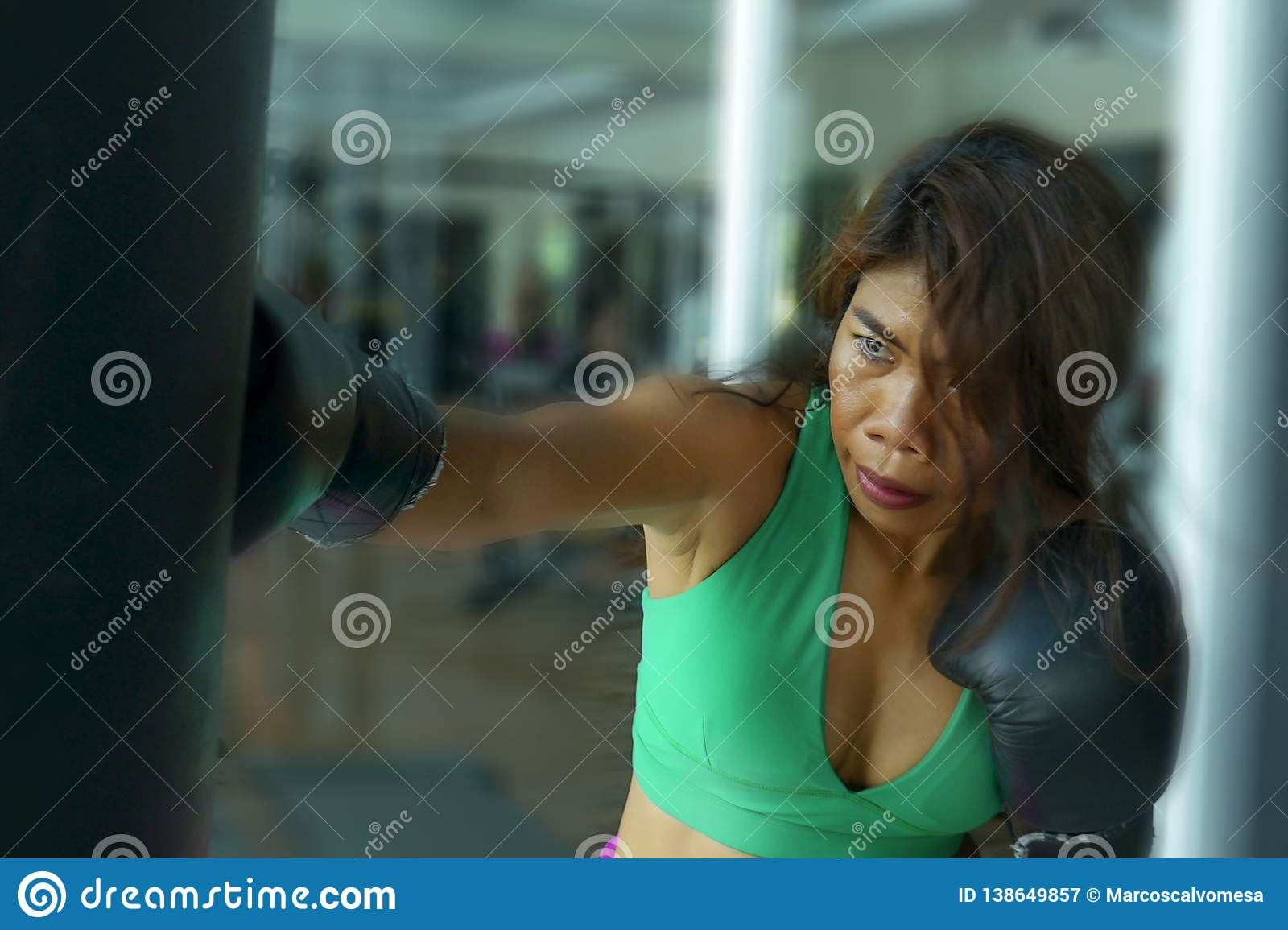 Young athletic and fit attractive Asian fighter woman punching heavy bag with boxing gloves at fight club gym doing hard workout