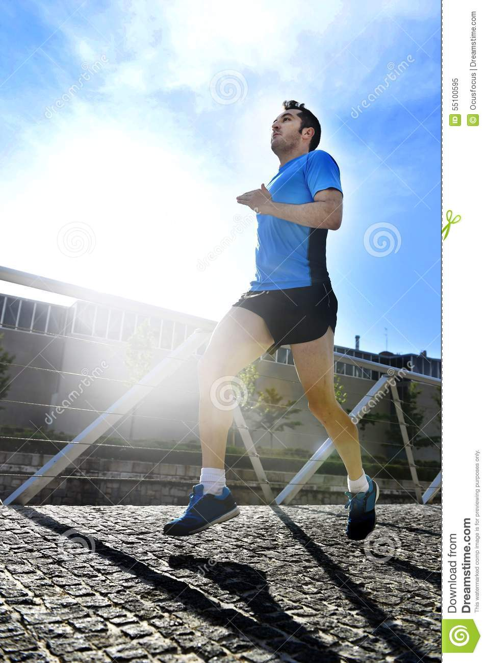 Young athletic man practicing running in urban background backlight in fitness sport training and healthy lifestyle concept