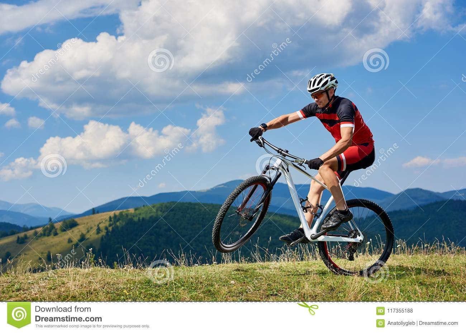 Young athletic sportsman tourist biker in professional sportswear turning on one wheel of bike