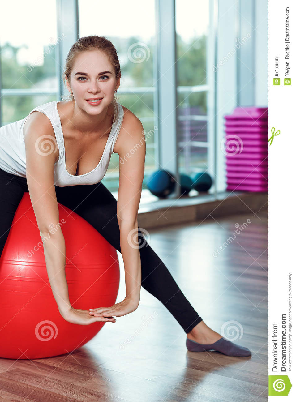 Young athletic woman doing exercises with fitness ball in gym