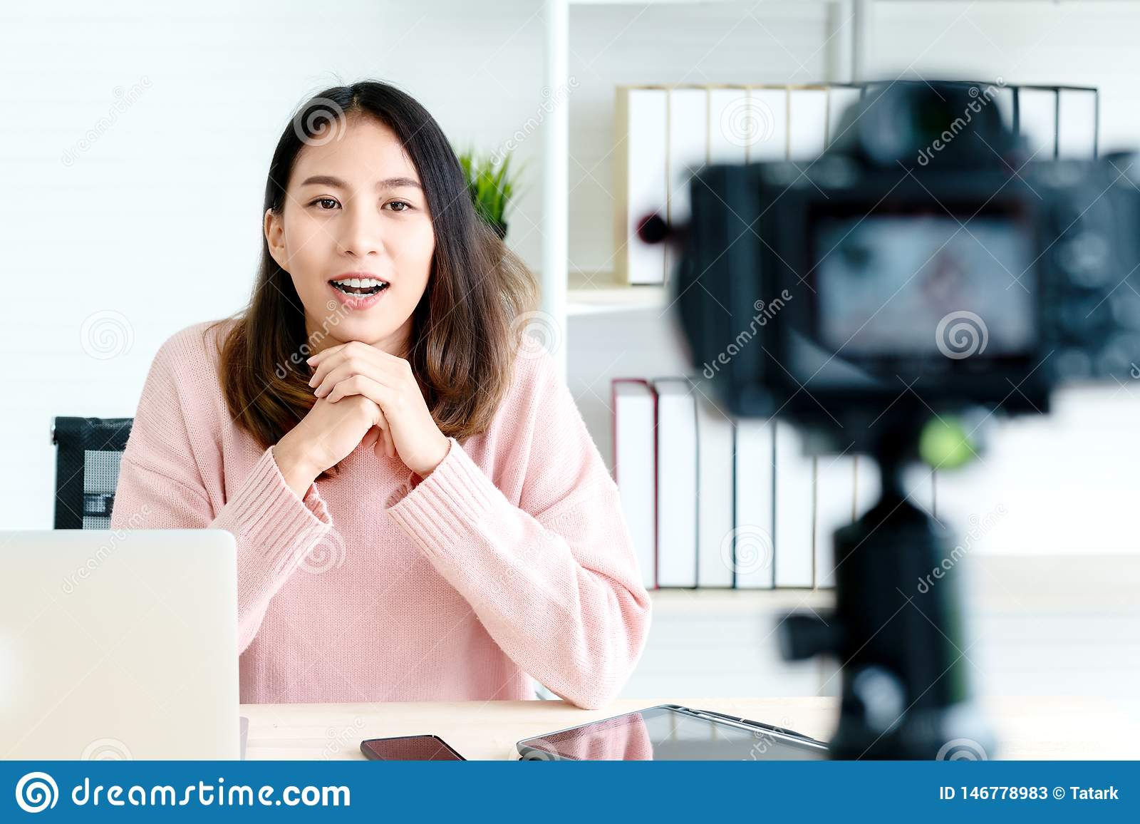 Young attractive asian woman blogger or vlogger looking at camera and talking on video shooting with technology. Social media