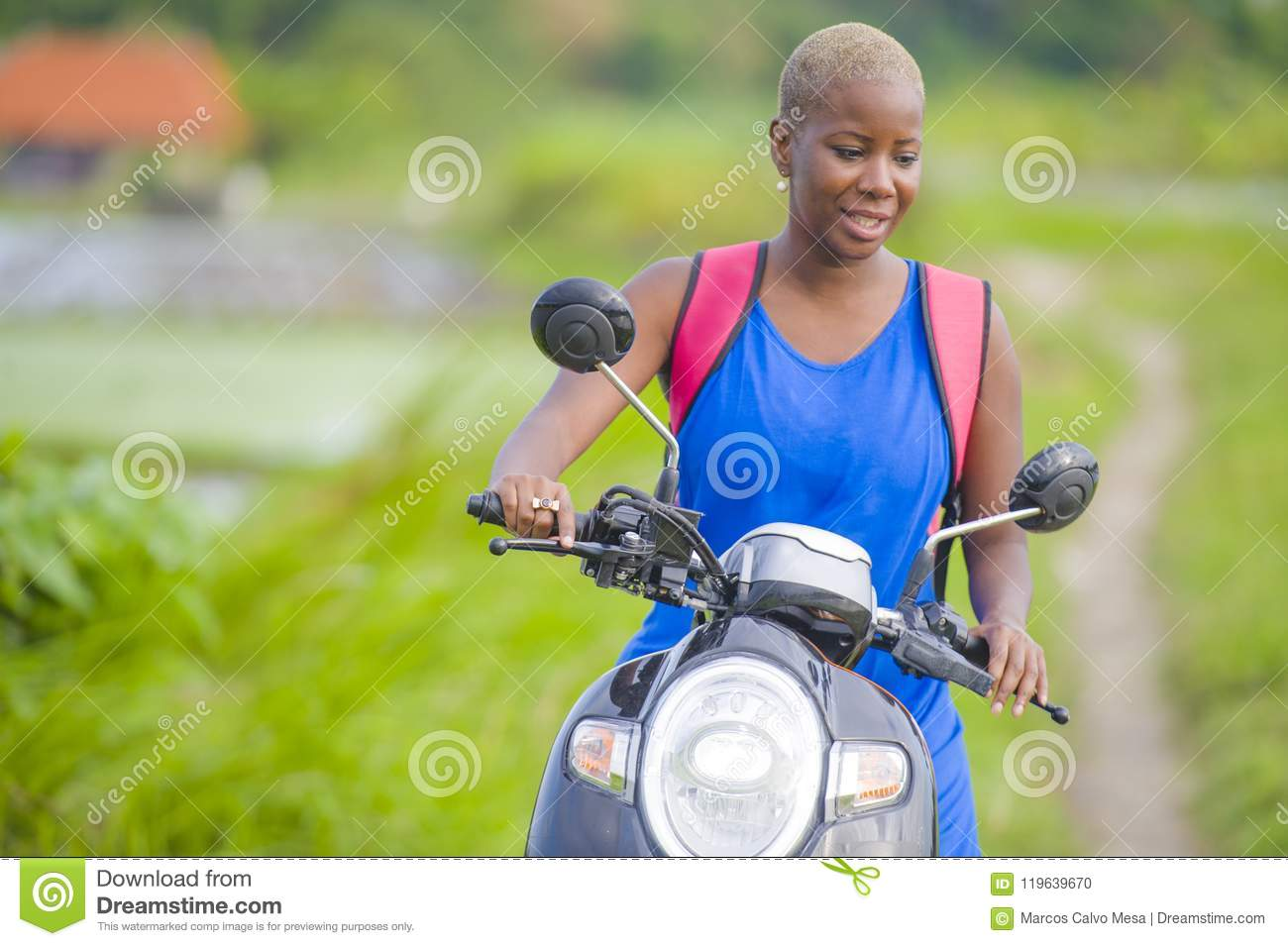 Young attractive backpacker tourist afro American black woman riding motorbike happy in beautiful Asia countryside along green ric