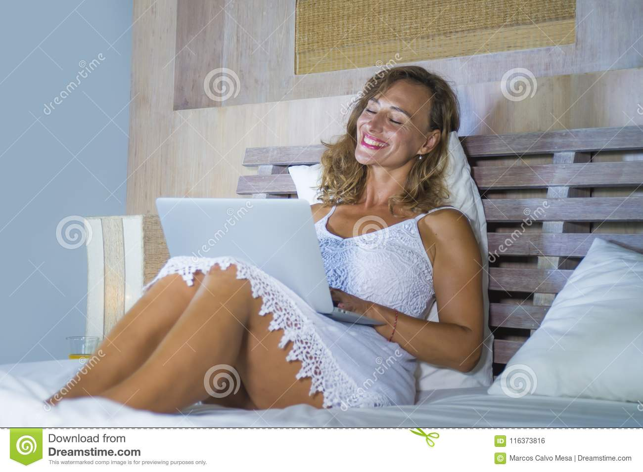 Young attractive and beautiful happy Caucasian woman 30s lying in bed at home using internet working on computer laptop smiling re