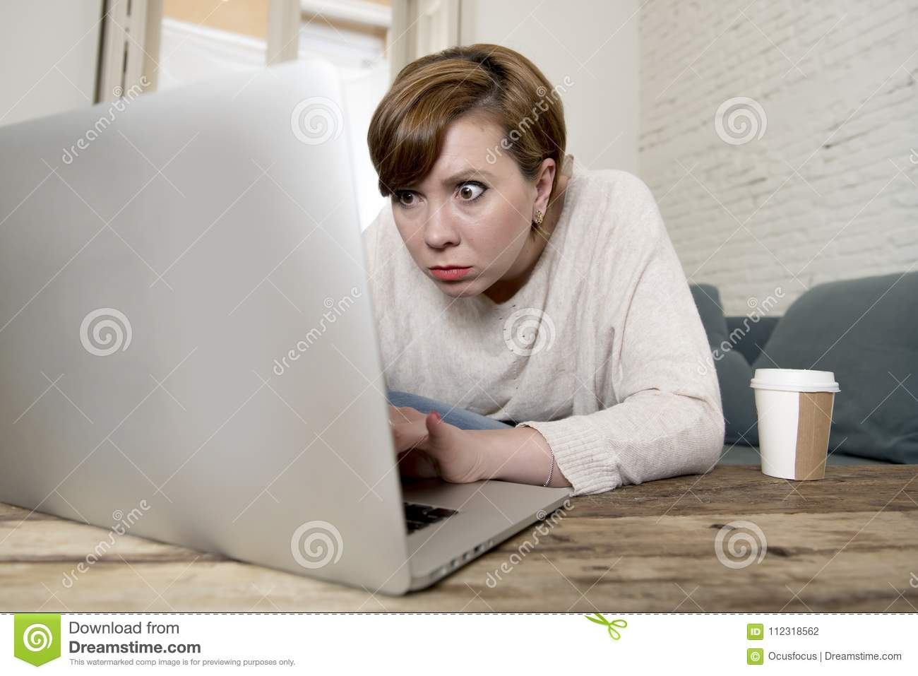 Young attractive and busy woman at home sofa couch doing some laptop computer work in stress looking worried in entrepreneur lifes