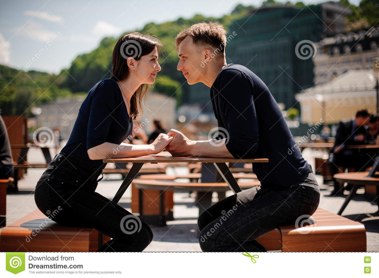 Young and attractive couple holding hands about to kiss over table in restaurant