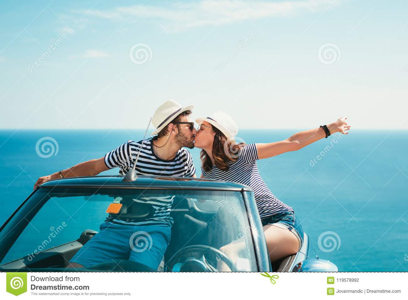 Young attractive couple posing in a convertible car