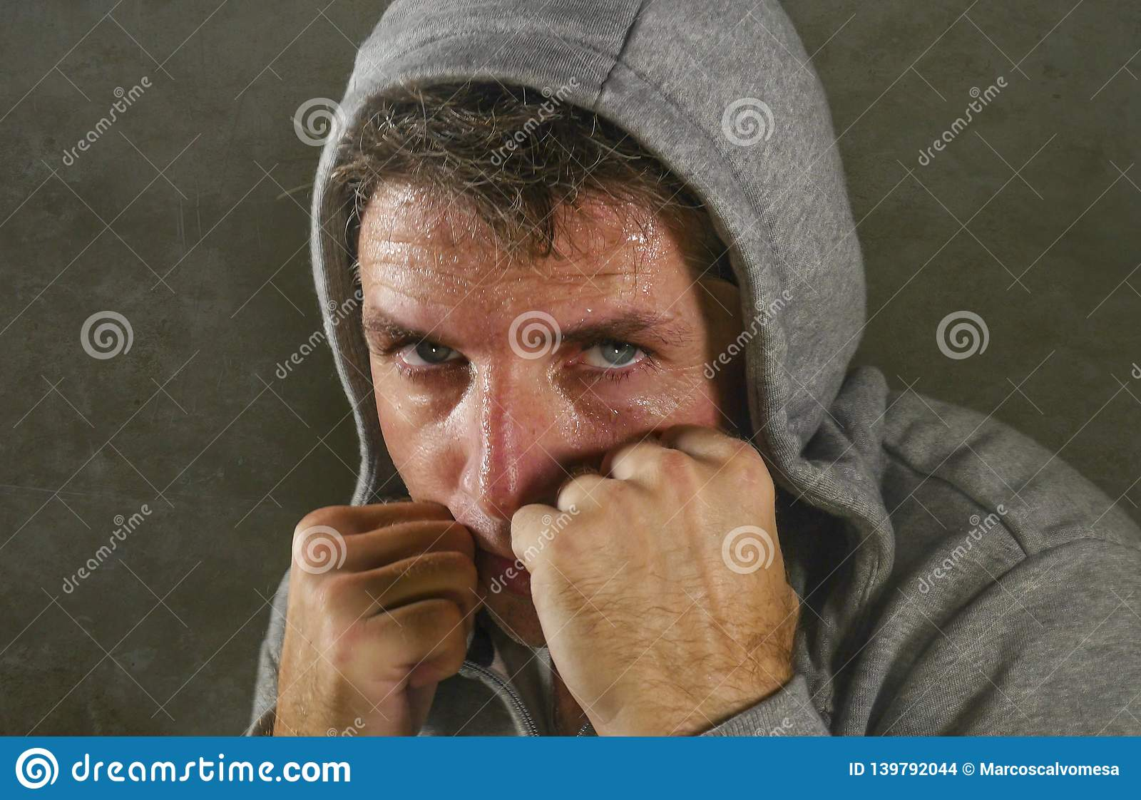 Young attractive and fierce looking man wearing hoodie posing in aggressive fighter stance isolated on dark background in sport