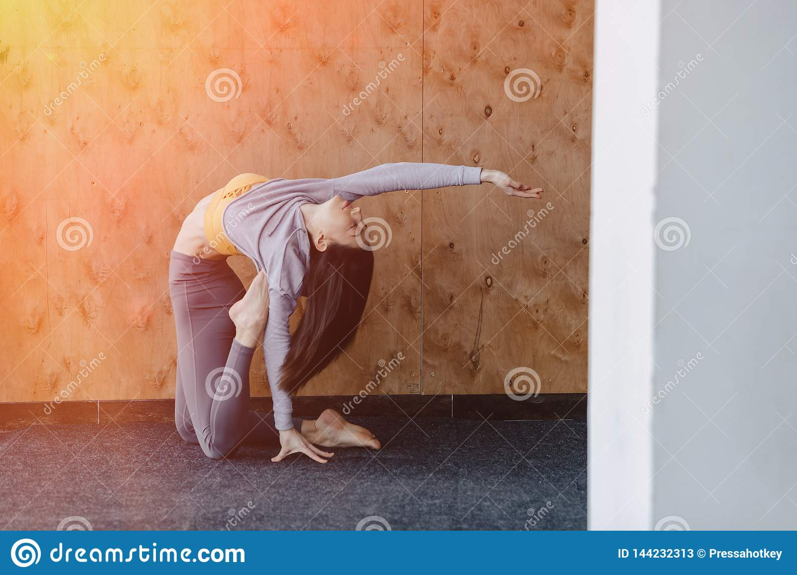 Young attractive girl doing fitness exercises with yoga on the floor on a wooden background